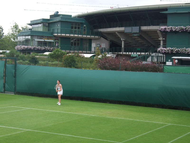 Dwarfed by the showcourt in the background, Amy Ellis is unfazed at the Road To Wimbledon.